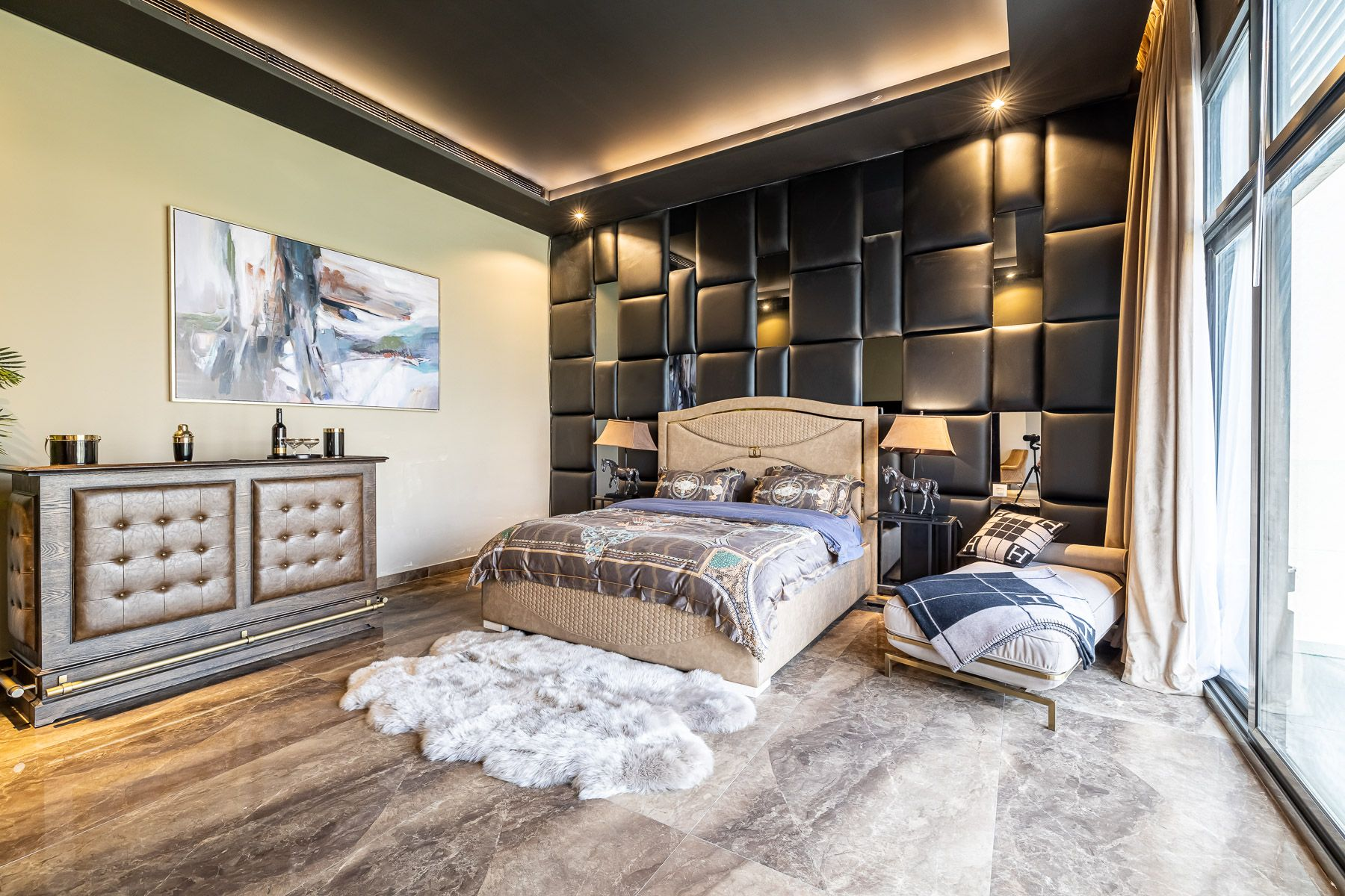 bedroom with brown marble floors and leather accent wall